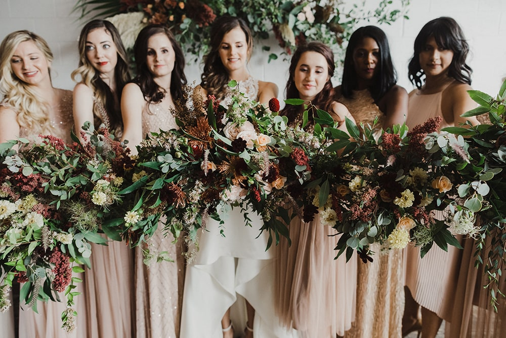 Bridesmaids holding bouquets toward camera