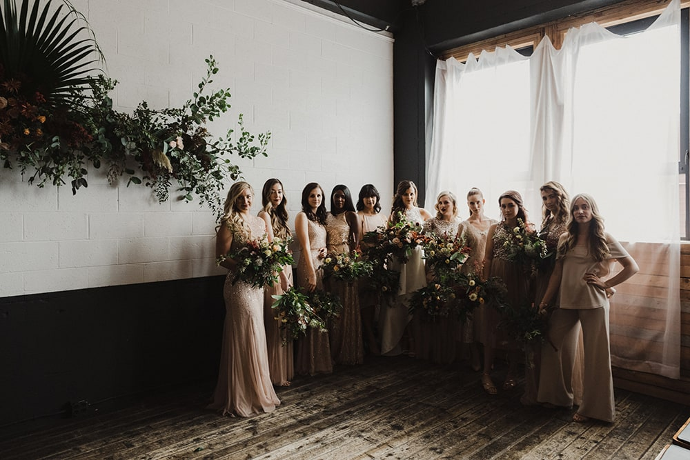 bridesmaids laughing and playing in front of window