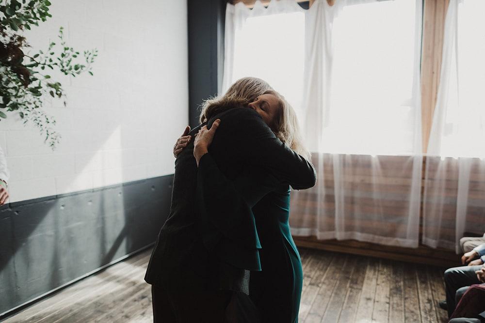 groom hugging mom before he marries his bride