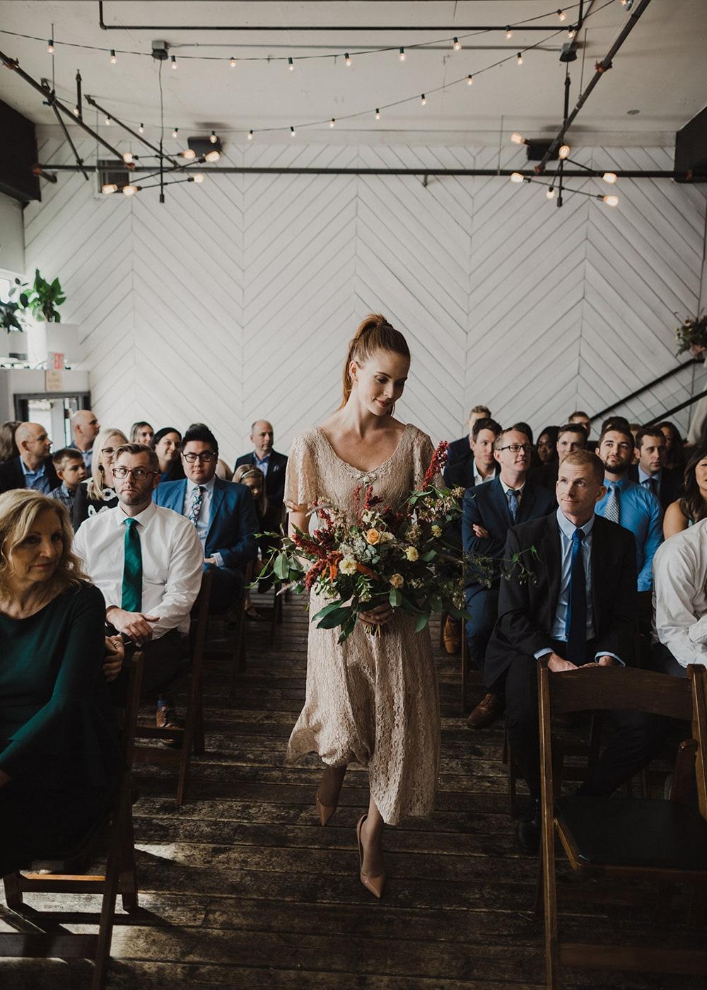 bridesmaid smiling looking down at flowers walking down isle