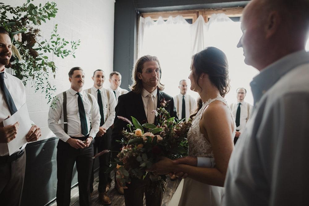 groom seeing bride after walking down isle smiling