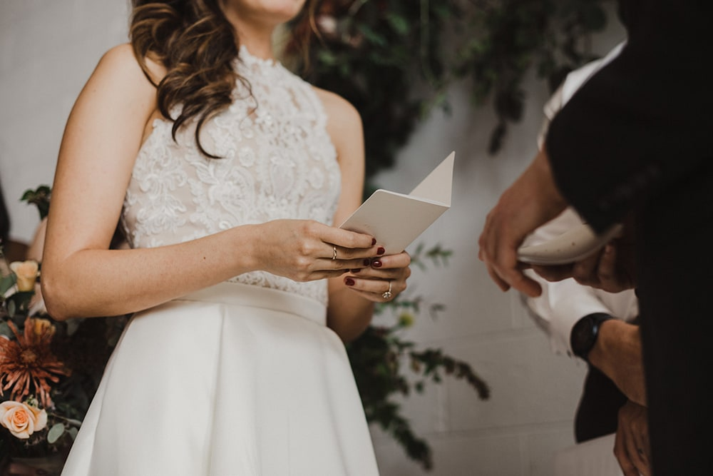 bride reading vows to groom during ceremony