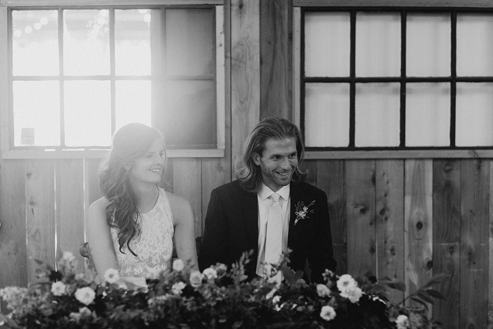 sunlight coming through barn doors with bride and groom