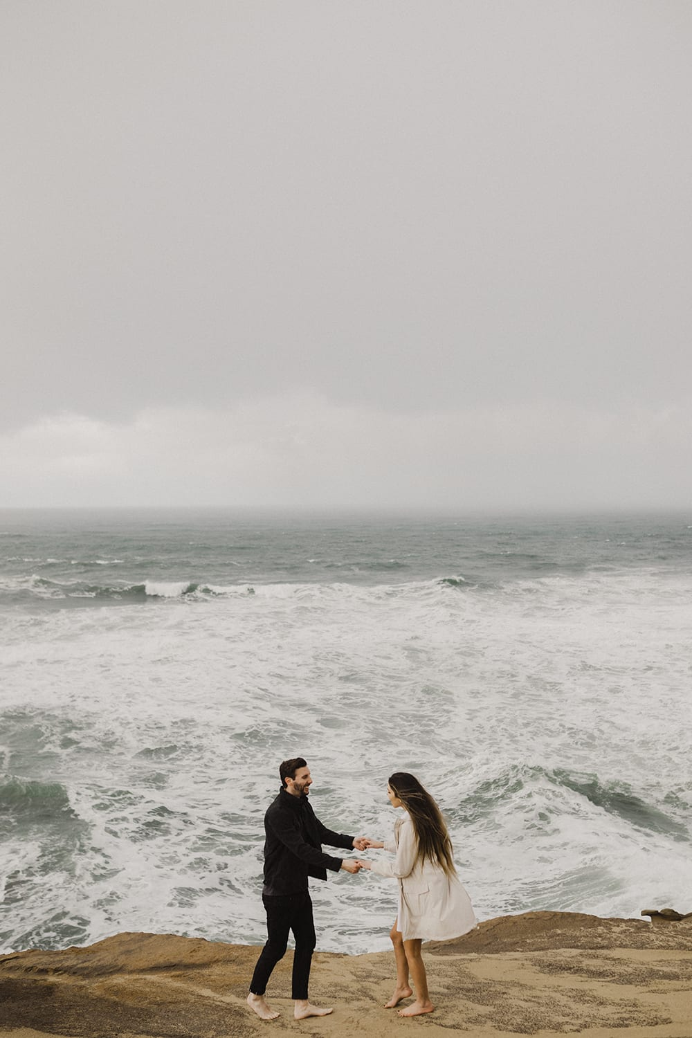 couple walking along oceanside with dramatic waves