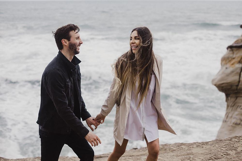 couple laughing and walking on oregon coast