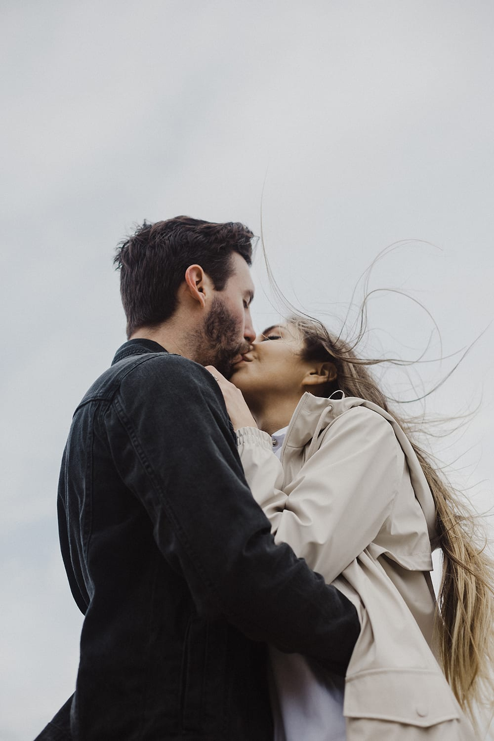 couple kissing with hair blowing in wind