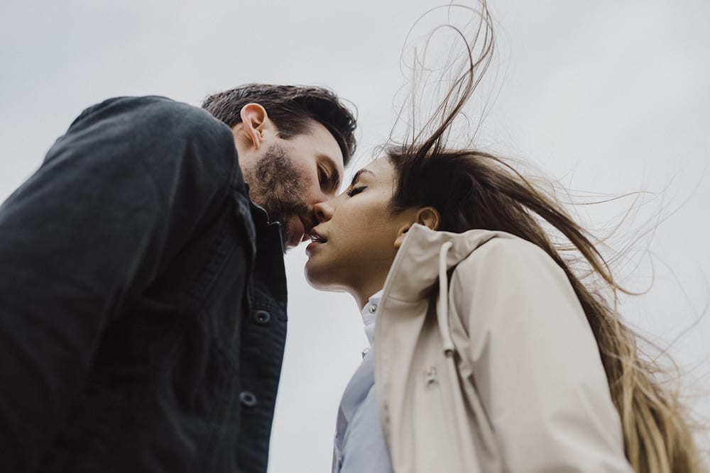 couple kissing with air blowing and noses touching