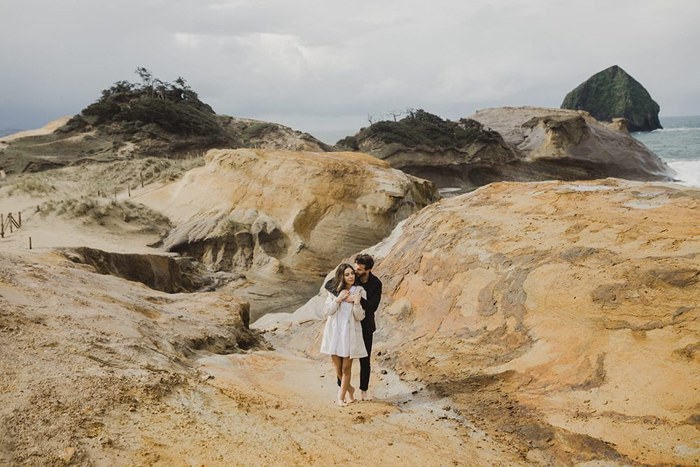 Couple standing in front of epic cape kiwanda backdrop