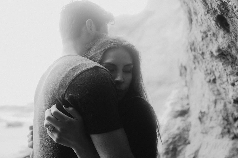 woman cuddling into man in black and white photo