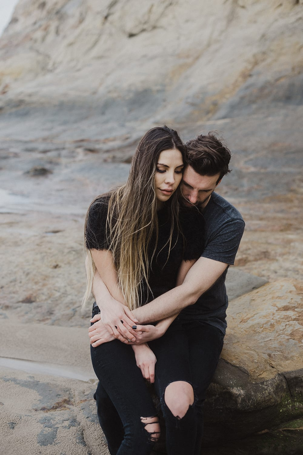 guy squeezing hugging girl ripped jeans long hair