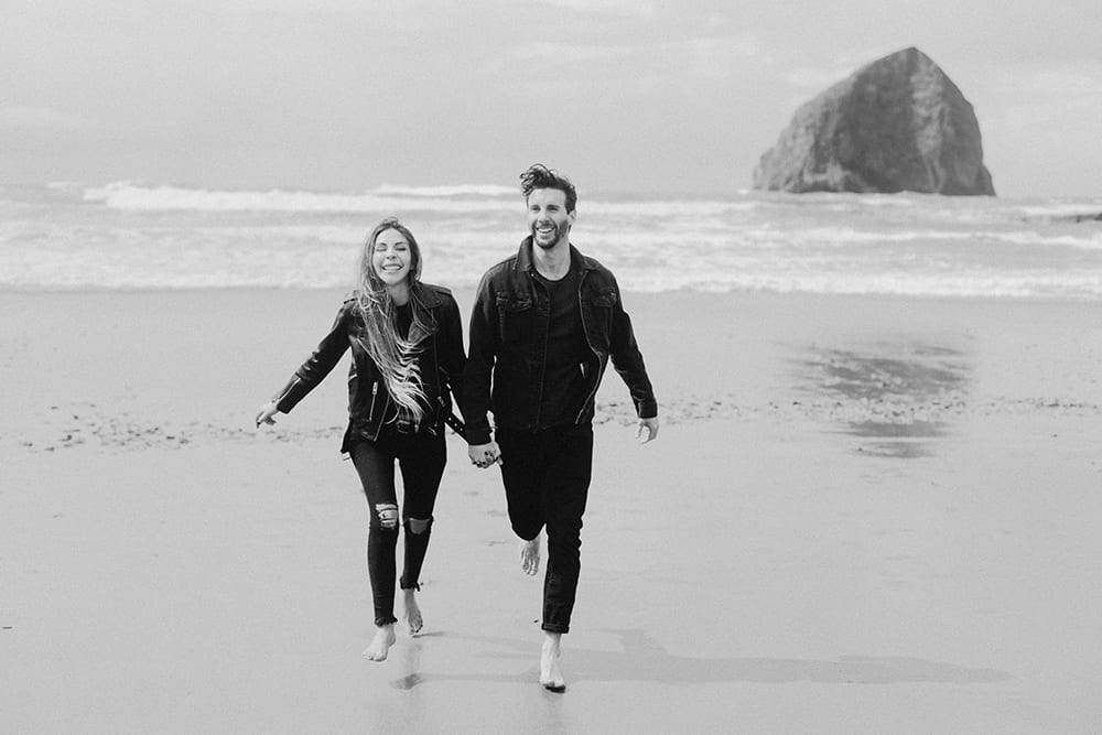couple running toward photographer in black and white photo