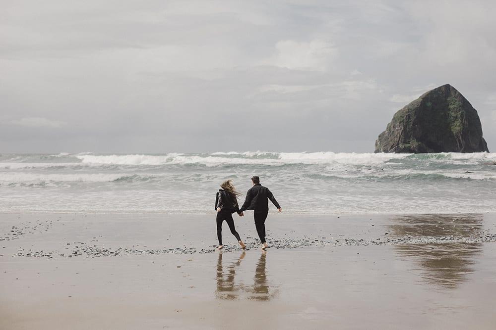 couple running along oceanfront