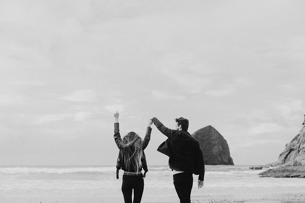 CCouple with hands in the air, excited on ocean on oregon coast