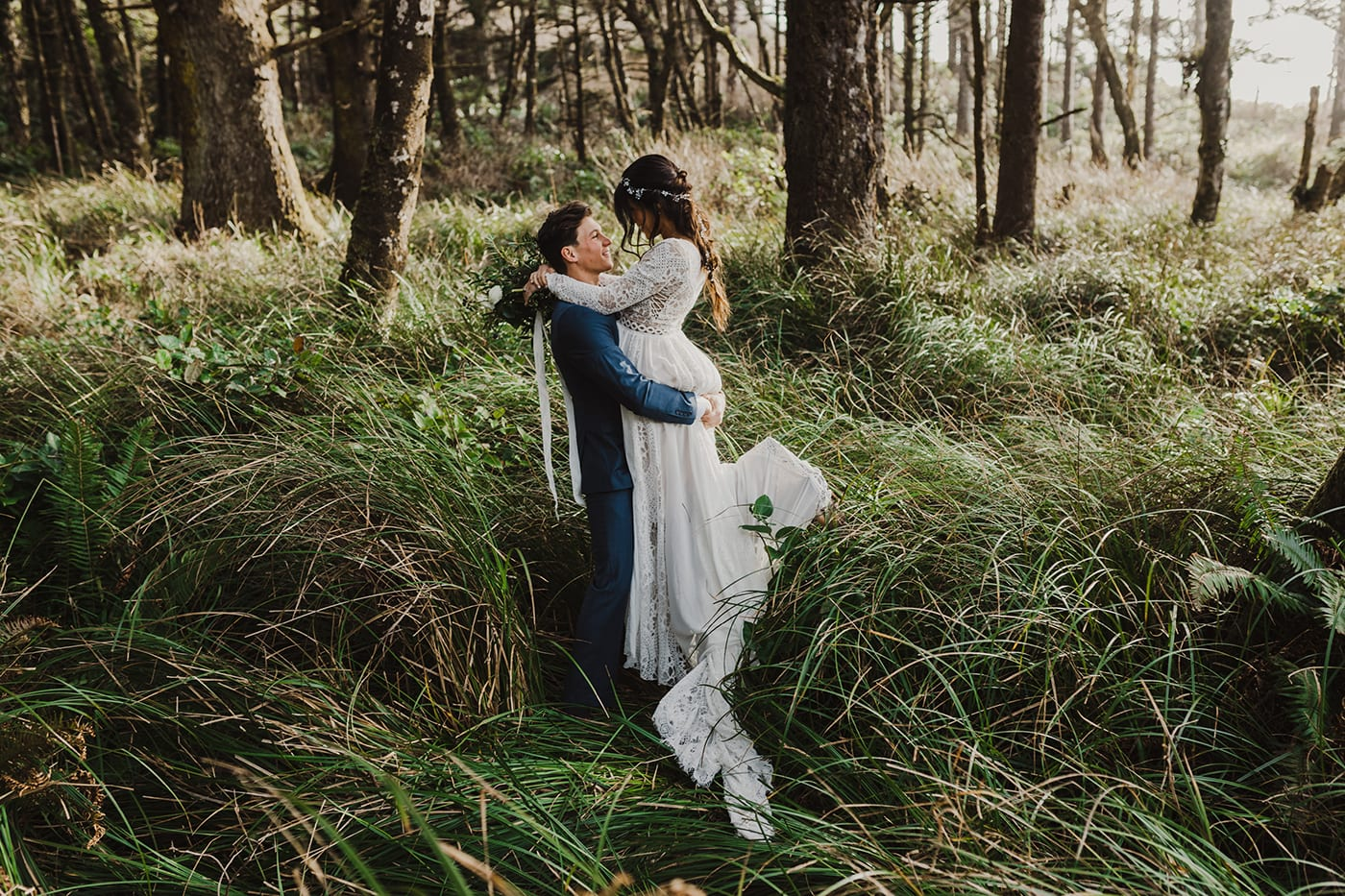Groom in blue suit picking up bride and kissing her in grass with trees