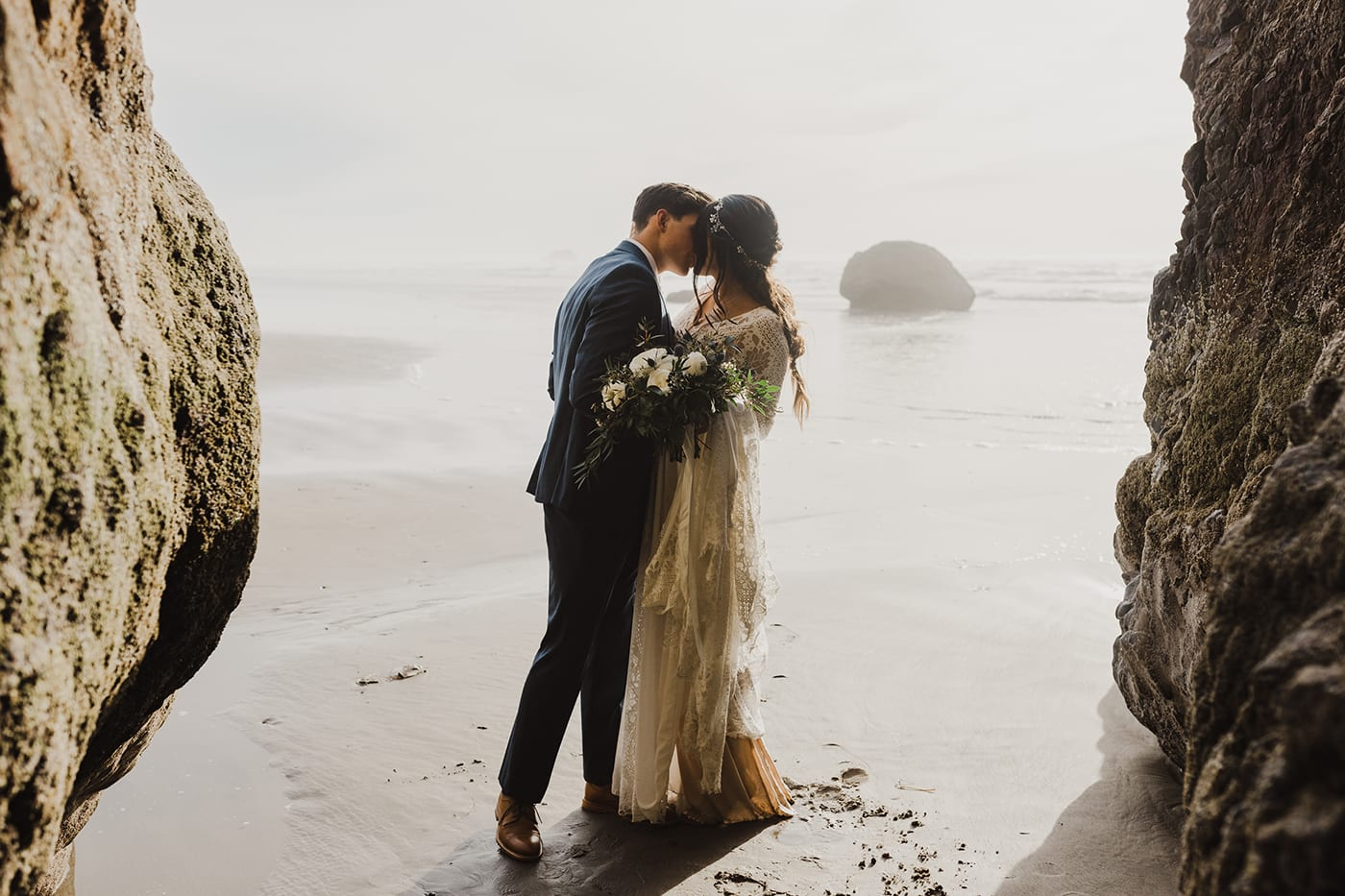 couple kissing in caves before elopement ceremony with ocean backdrop
