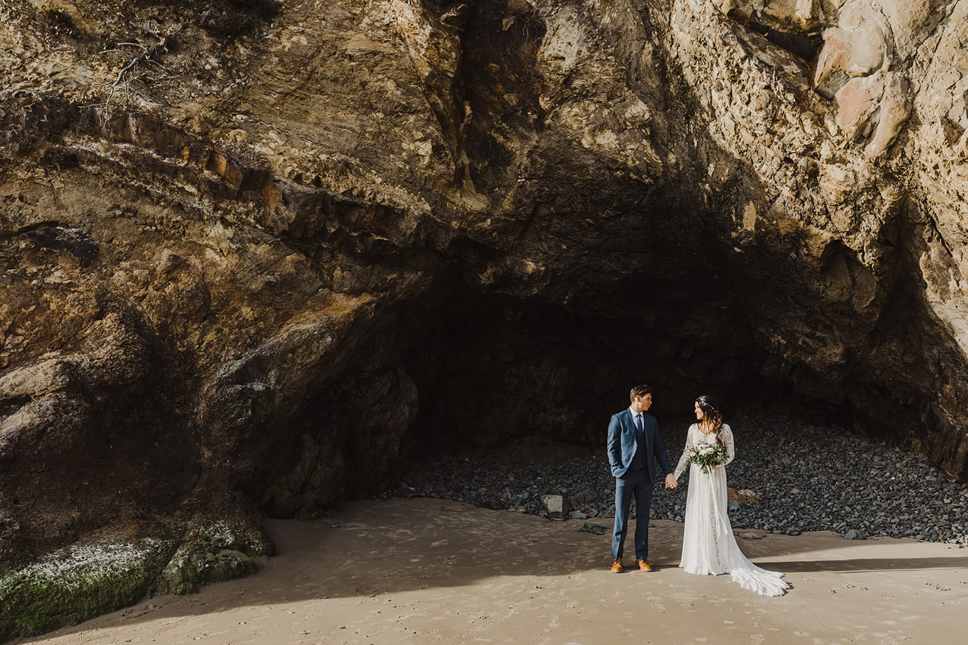 large rock formation with cave and couple standing in front holding hands before elopement