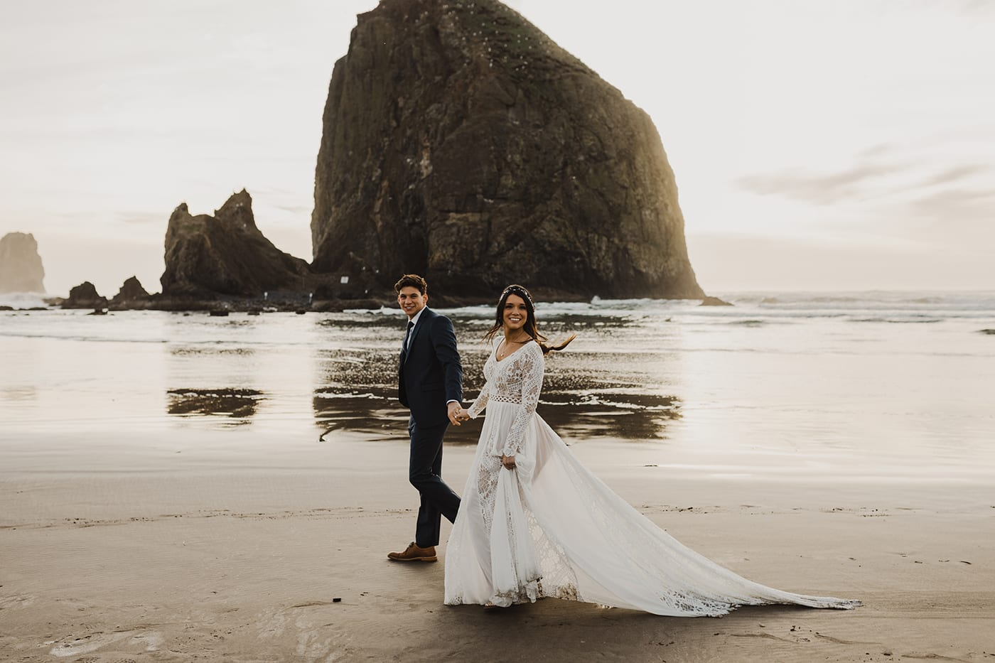 couple walking down beach with sunset in background after eloping