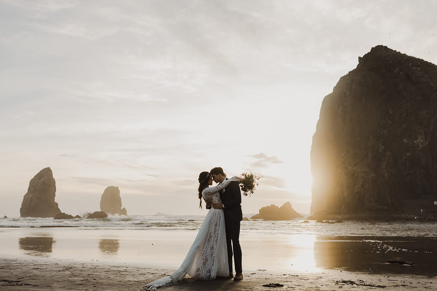 couple kissing on cannon beach before wedding ceremony and elopement