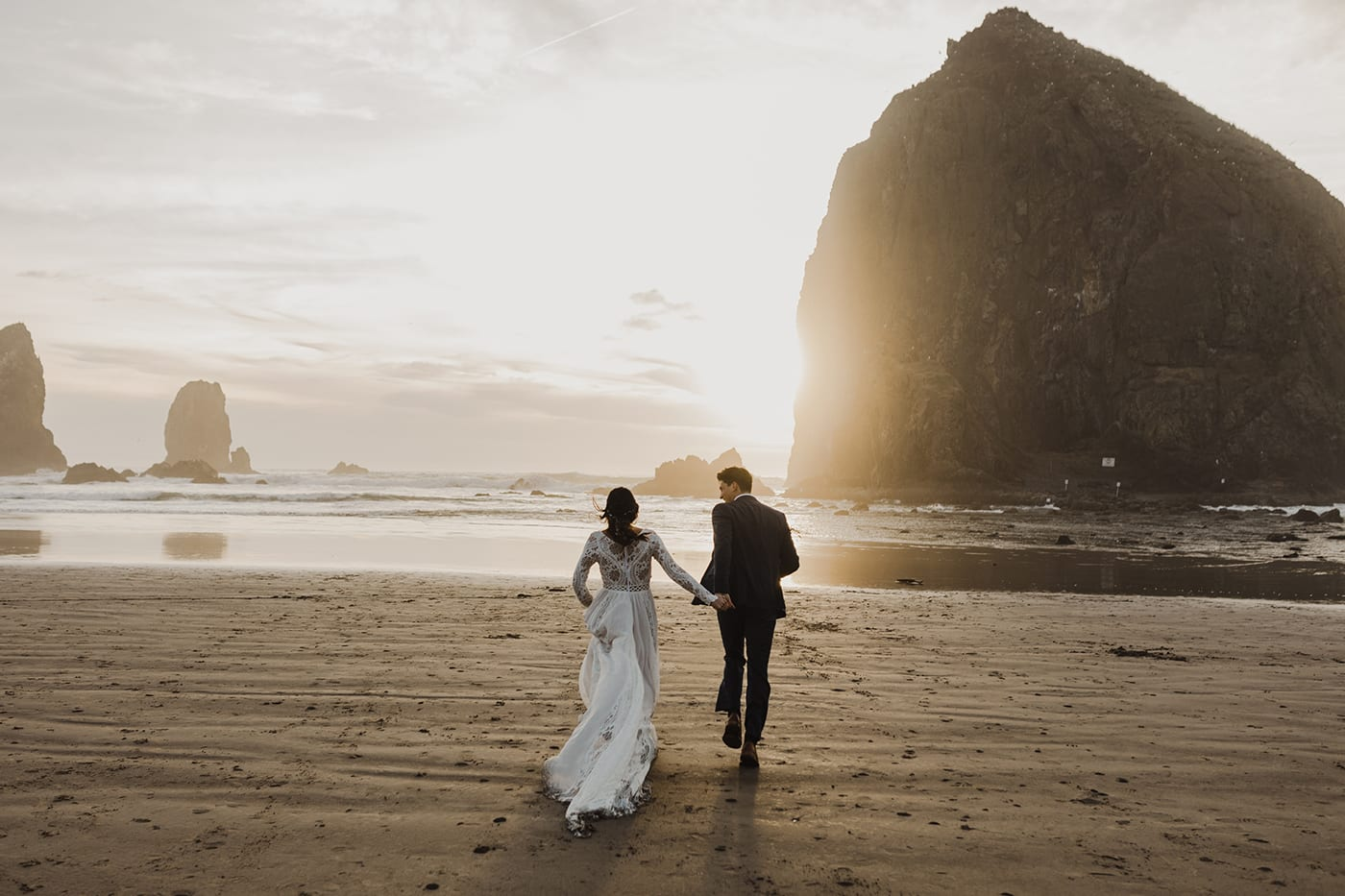 bride and groom running toward ocean with sunset and haystack rock