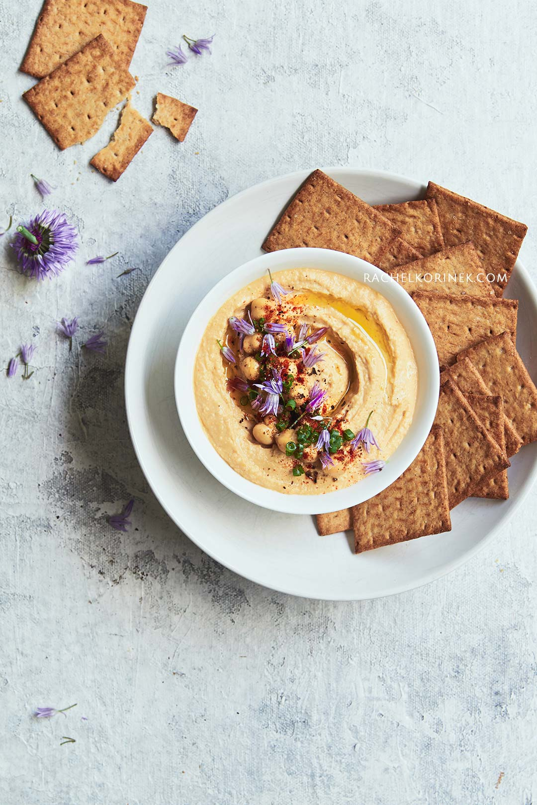 Rachel Korinek Food Photographer   Hummus With Chive Flowers  Click to check out my latest food photography projects.  #twolovesstudio #beautifulcuisine #foodbloggerpro #foodphotography #learnfoodphotography #foodblogger #learnphotography #foodstyling #lightingtips #naturallight #foodphotographer