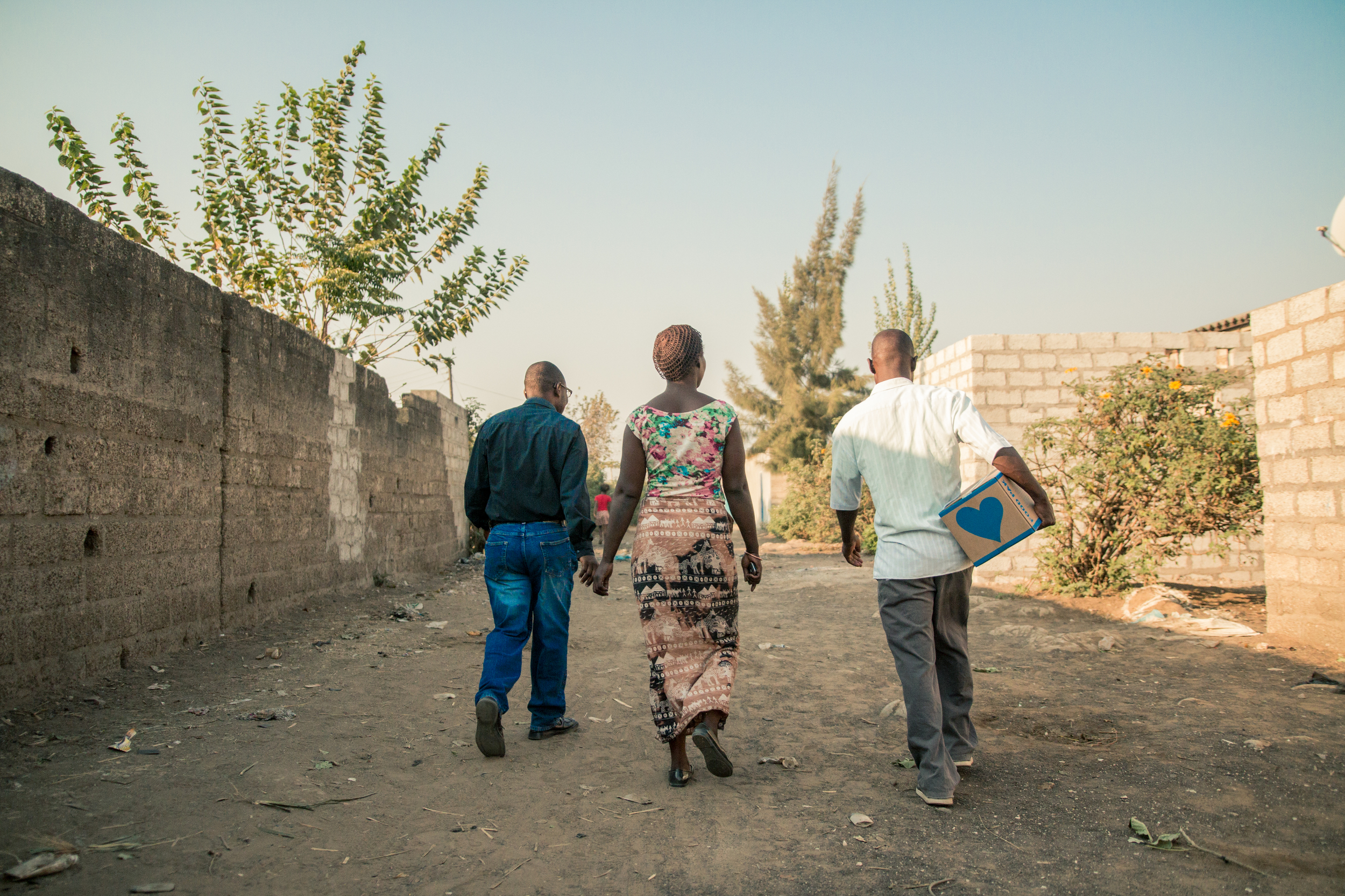 ZAMBIA: [Home Visit] Pastor German and friends walking through John Laing to deliver the first Food Pak.