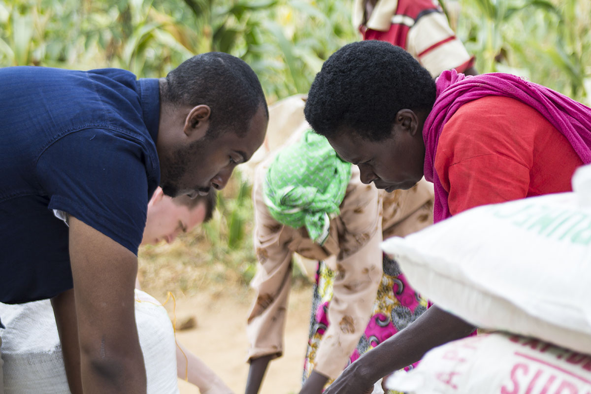 RWANDA: [Food Distribution] Some of the food recipients come to an evangelistic outreach at the church and after a short bible study receive bulk food. It was a joy to serve them, getting down on our hands and knees to fill their sacks with a months supply of food.