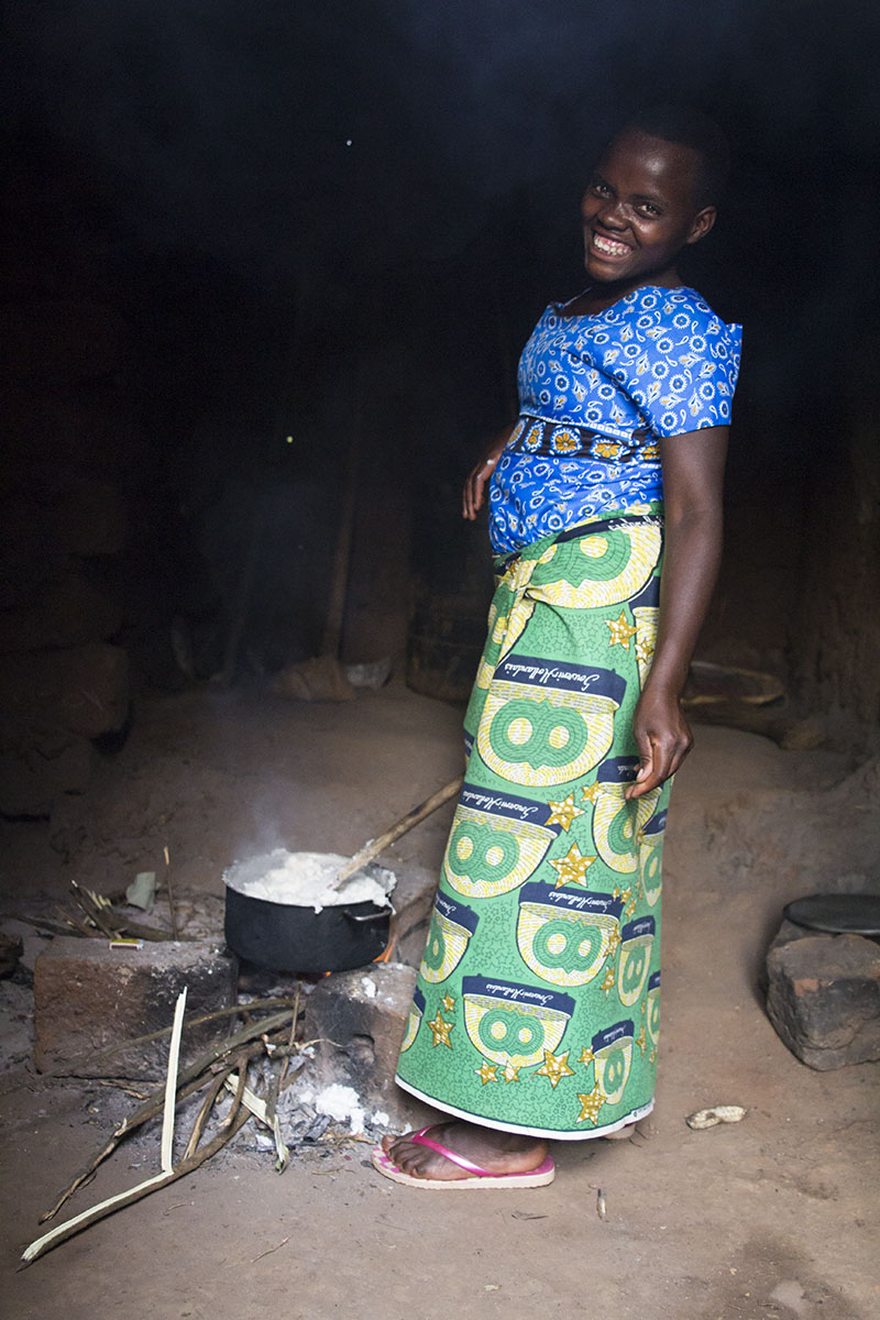 RWANDA: [Home Visit] Nakabonye's 12 year old daughter cooked a meal for the whole family. There was so much smoke from the burning straw inside the hut that we couldn't stand it. She just smiled and laughed at us.