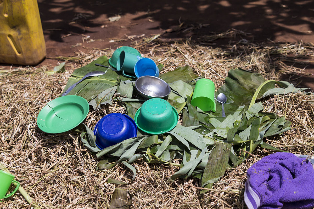 UGANDA: [Home Visit] This family was so excited to receive us as house guests that they washed their best dishes and laid them out on banana leaves to dry for supper.