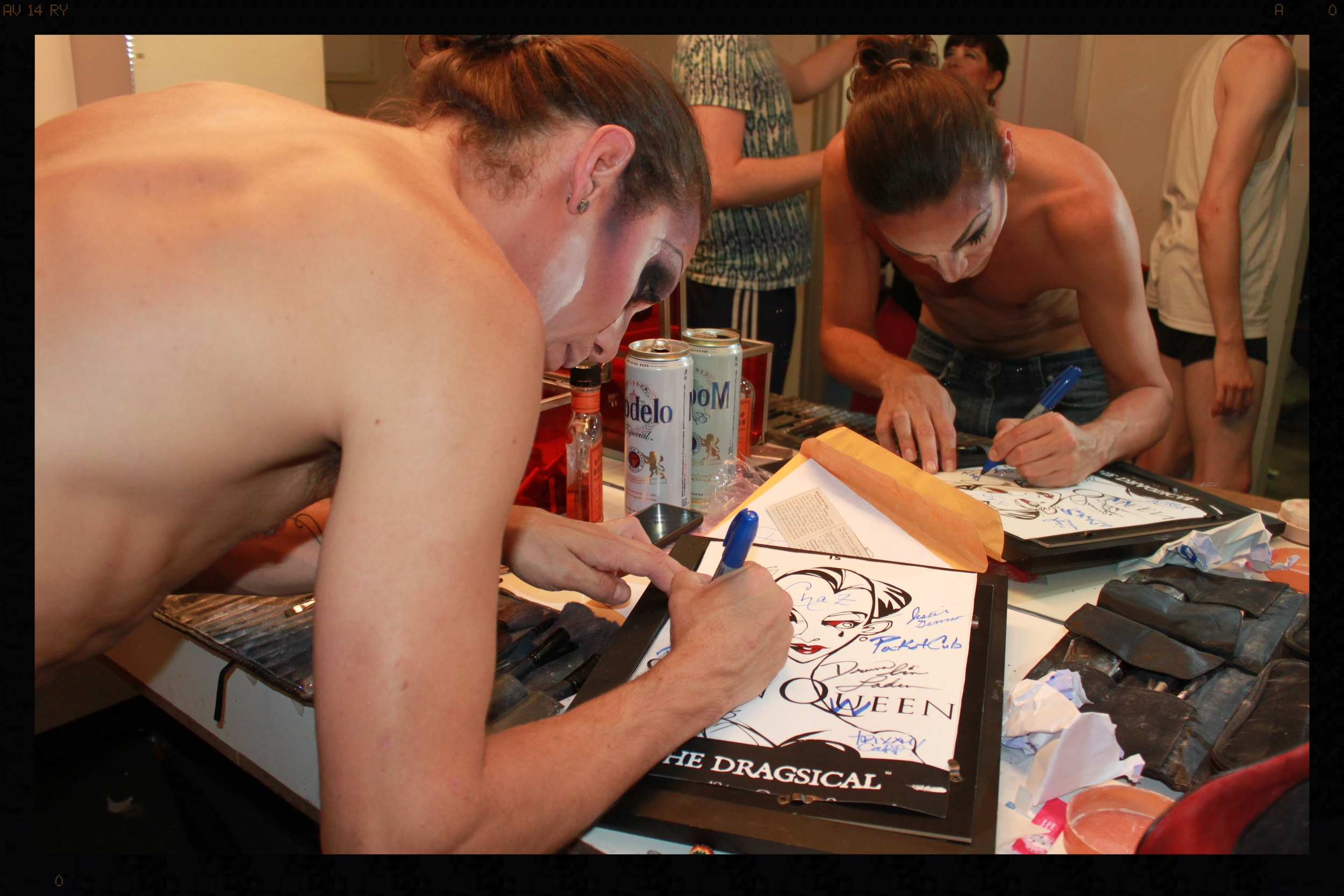 Doing it.   Suppositori Spelling  signs a Swan Queen poster to be raffled for charity on opening night.