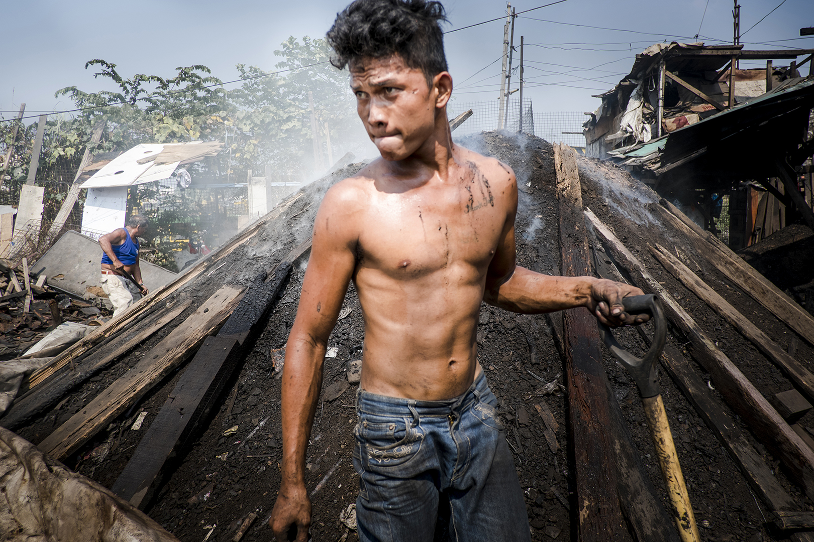 Andrei (20) lives in a dumpsite area of Malabon, one of the poorest and most dangerous slums in Metro Manila. He started working in a community produced coal business at the age of 14. He works 7 days a week and earns around 3 euro per day. It takes 2 weeks to prepare coal ready for sale; employees are paid only when everything is sold. Malabon, Metro Manila, 2017