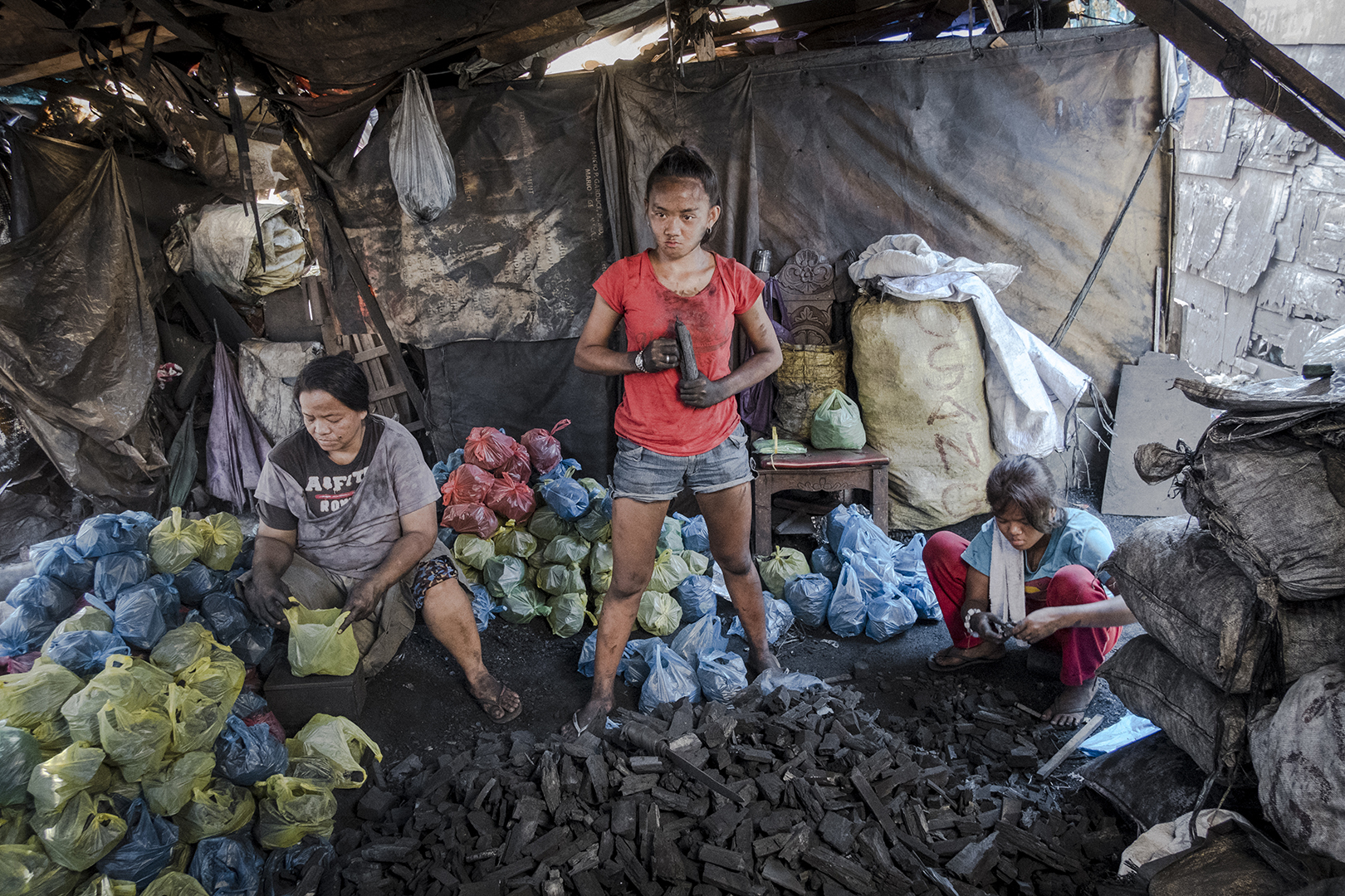 Jane-Rosa (16) stopped school at the age of 14. She is the oldest of 4 kids and works to help her parents sustain their family. She has recently moved into her boyfriends, Andrew who also works at the charcoal production, family house. Malabon, Philippines, 2017