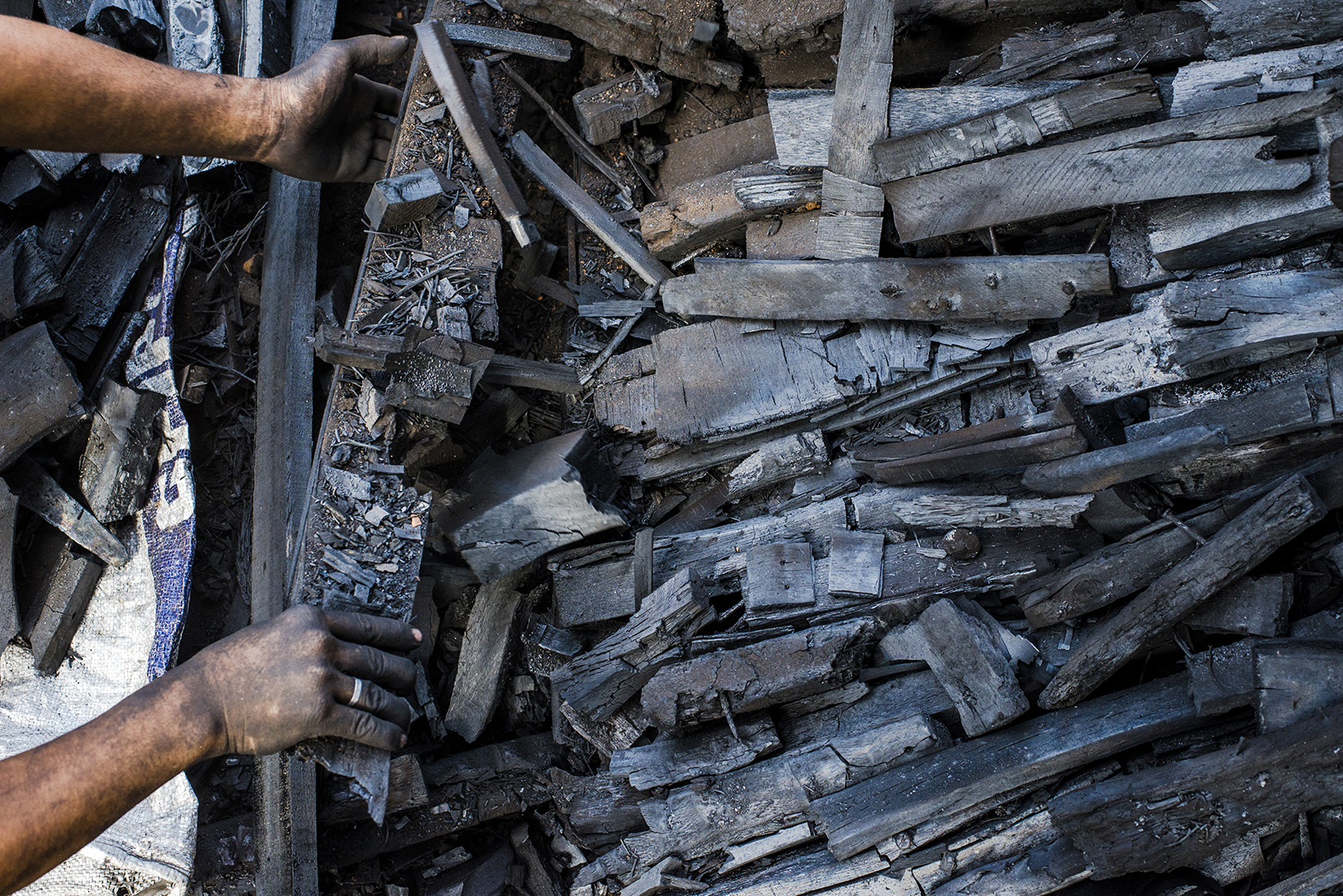 Nails and metal parts are separated and collected in the final process of charcoal production. Mostly women and girls collect them as an extra income. One kilo of nails is sold for 10 pesos in a Junk Shop near by. Malabon, Philippines, 2017