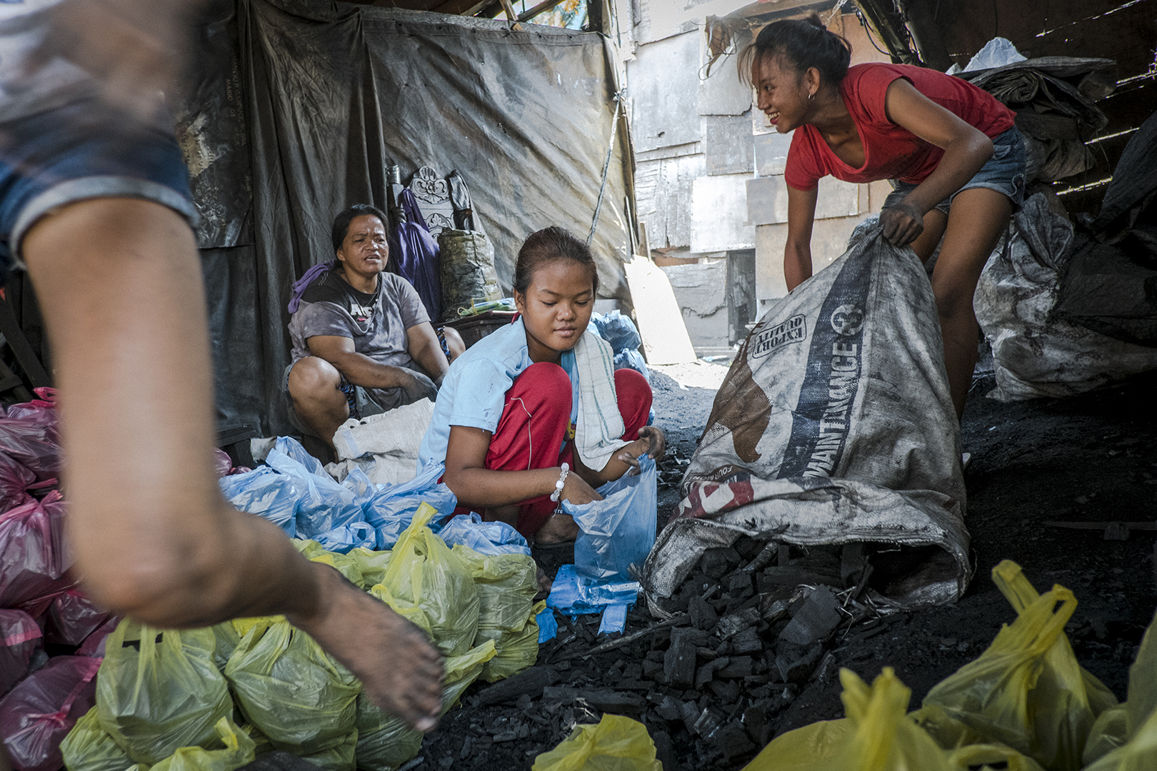 Larisa (14) works at the charcoal factory 5 days a week. She stopped school a few years ago. She doesn't have an official birth certificate and therefore cannot officially sign for classes. The local school head master agreed to accept her for one more year after which she will stop her education. Her sister, Larisa (13) who also work at the charcoal production has hearing difficulties, as the family have no funds to pay for the check up and the treatment. Malabon, Philippines, 2017