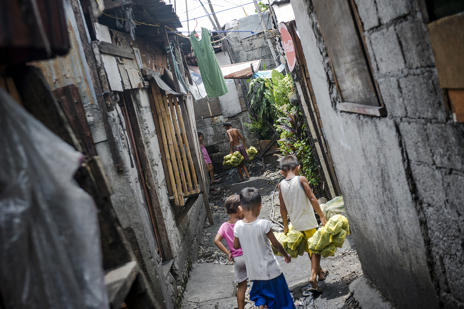 Kids in the community start helping their parents from a very early age. The youngest to be paid for their work are about 7- 8 years old, but even earlier kids help their older siblings and parents, they live in the area and are constantly exposed to the toxic smoke. Malabon, Philippines, 2017