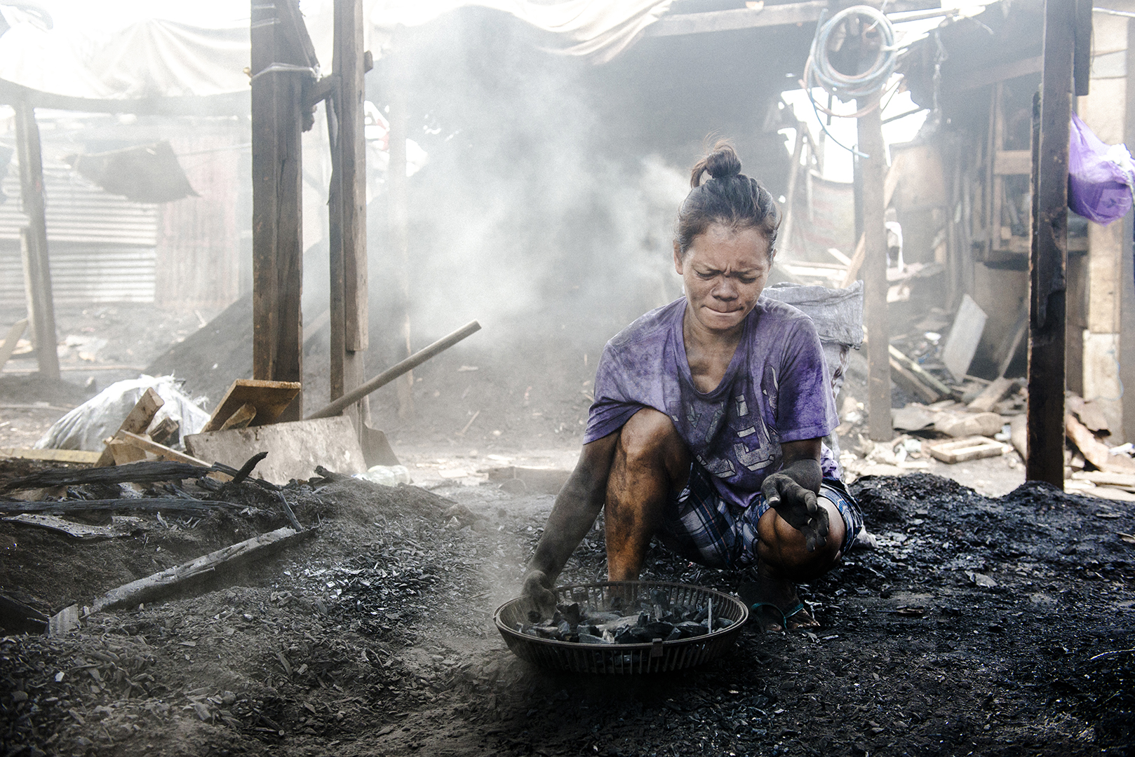 Christine (31) has 5 kids. She works in the charcoal production since 5 years to help her husband. Before she was staying at home. This time she helped to pack small pieces of call into the bags. It is for her the most difficult part, as she has to kneel all the time and sharp metal parts cut her hands. For five days of work she will earn 300 pesos. Malabon, Philippines, 2017