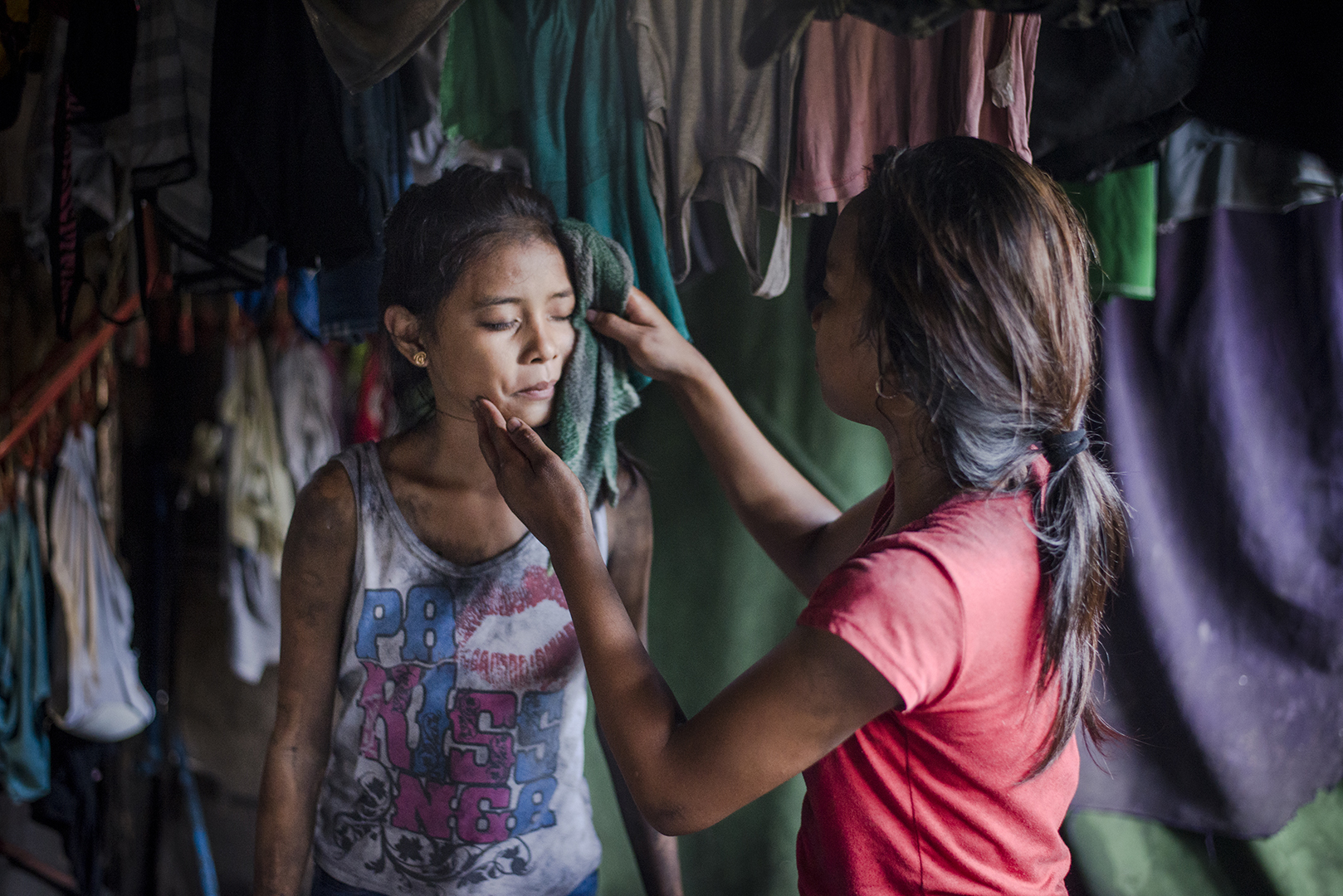 Jane-Rosa (16) and Shira (13) help each other wash up after a day of work in the local charcoal production. Girls know each other since a long-time, they live nearby, work and play together. Malabon, Philippines, 2017