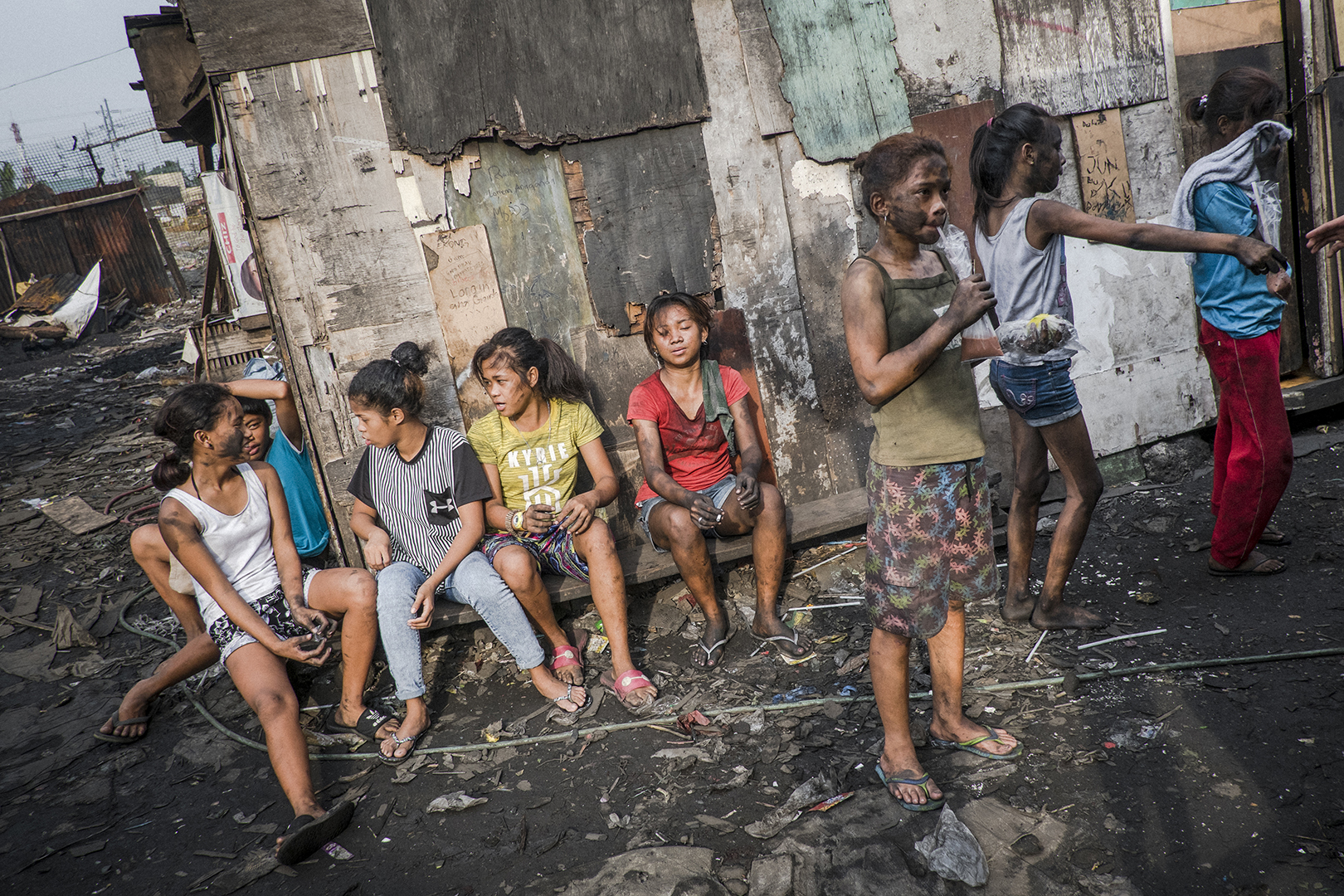 Girls taking rest after a long day of work, while boys are packing bags full of charcoal on the tricycles. They will later transport it to the local market where charcoal is being sold. Malabon, Philippines, 2017