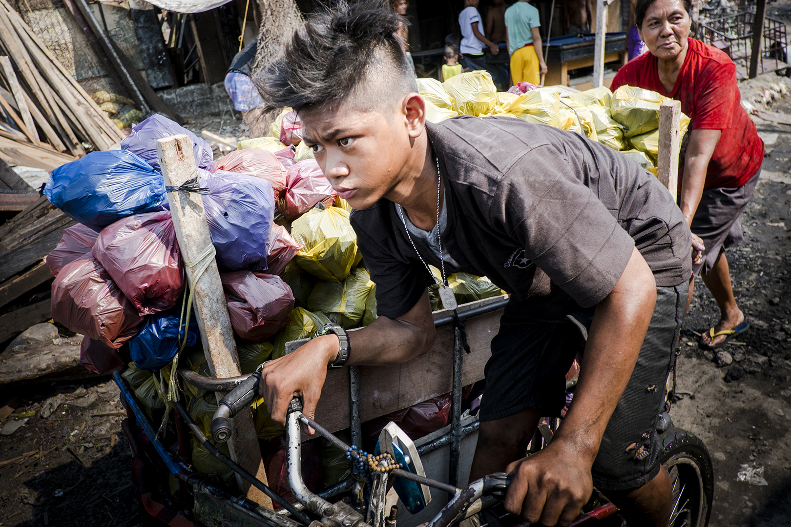 Young boy from the Ulingan community is transporting bags of charcoal to a local market where it is going to be sold. Most of young employees of the factories are being paid only when the charcoal is sold and when the owner of a local business is back the money that he or she invested in the wood used for the production. Malabon, Philippines, 2017