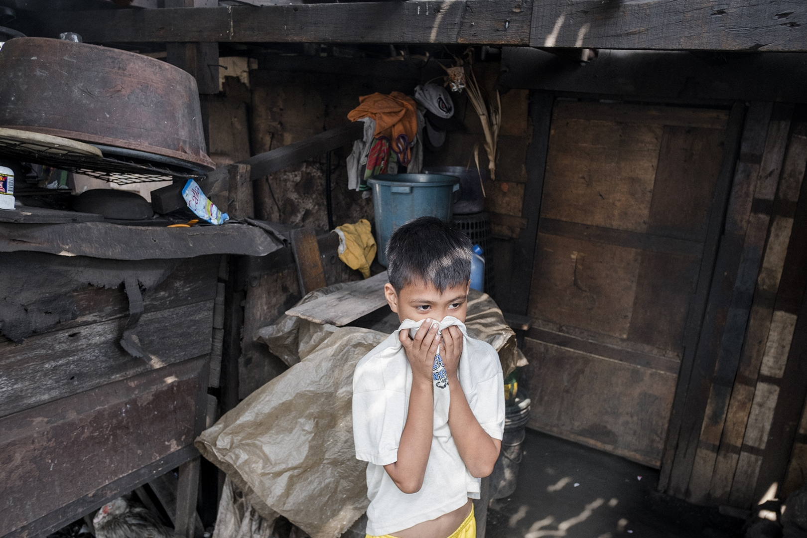 Boy who visits his uncle in the Ulingan community in Malabon covers his face to protect himself from the smoke floating in the air. Malabon, Philippines, 2017