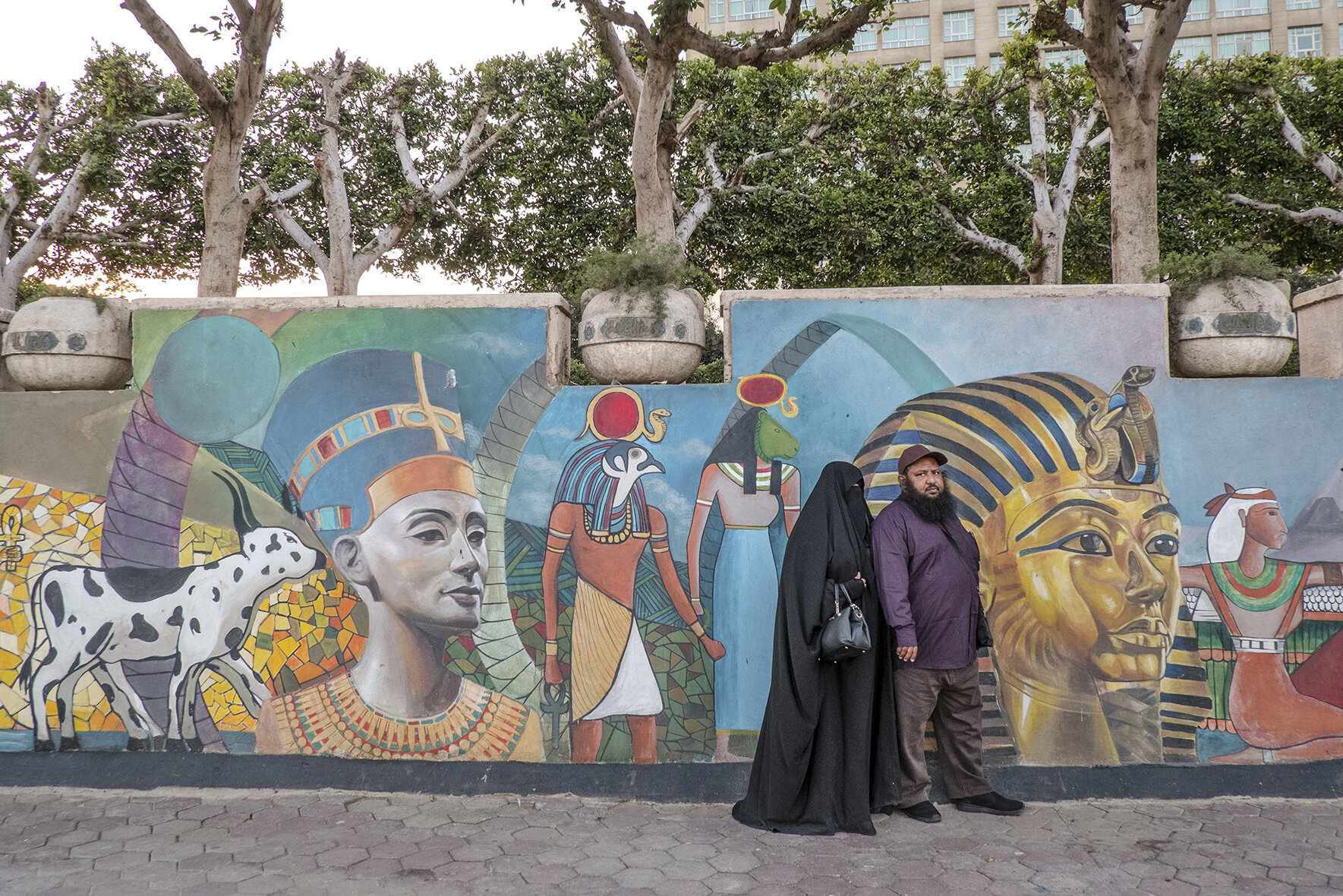 A religious Egyptian couple posing in front of a street paining in Cairo park located close to Tahrir square and Kasr Al Nile Bridge, where revolution against the previous regime started in 2011. During the year that followed, the Muslim Brotherhood, party which came to power, did everything they could to prevent gender equality and bring back the deep islamisation of the country.Among other plans their political agenda included: lowering the minimum age for marriage from 18 to 12, abolishing women's right to divorce and decriminalizing the practice of female genital mutilation.After Abdel Fattah El-Sisi become president some of those laws were changed but the budget for sexual education and family planning was lowered and several collaborations with international organisations were suspended. December 2018, Cairo, Egypt