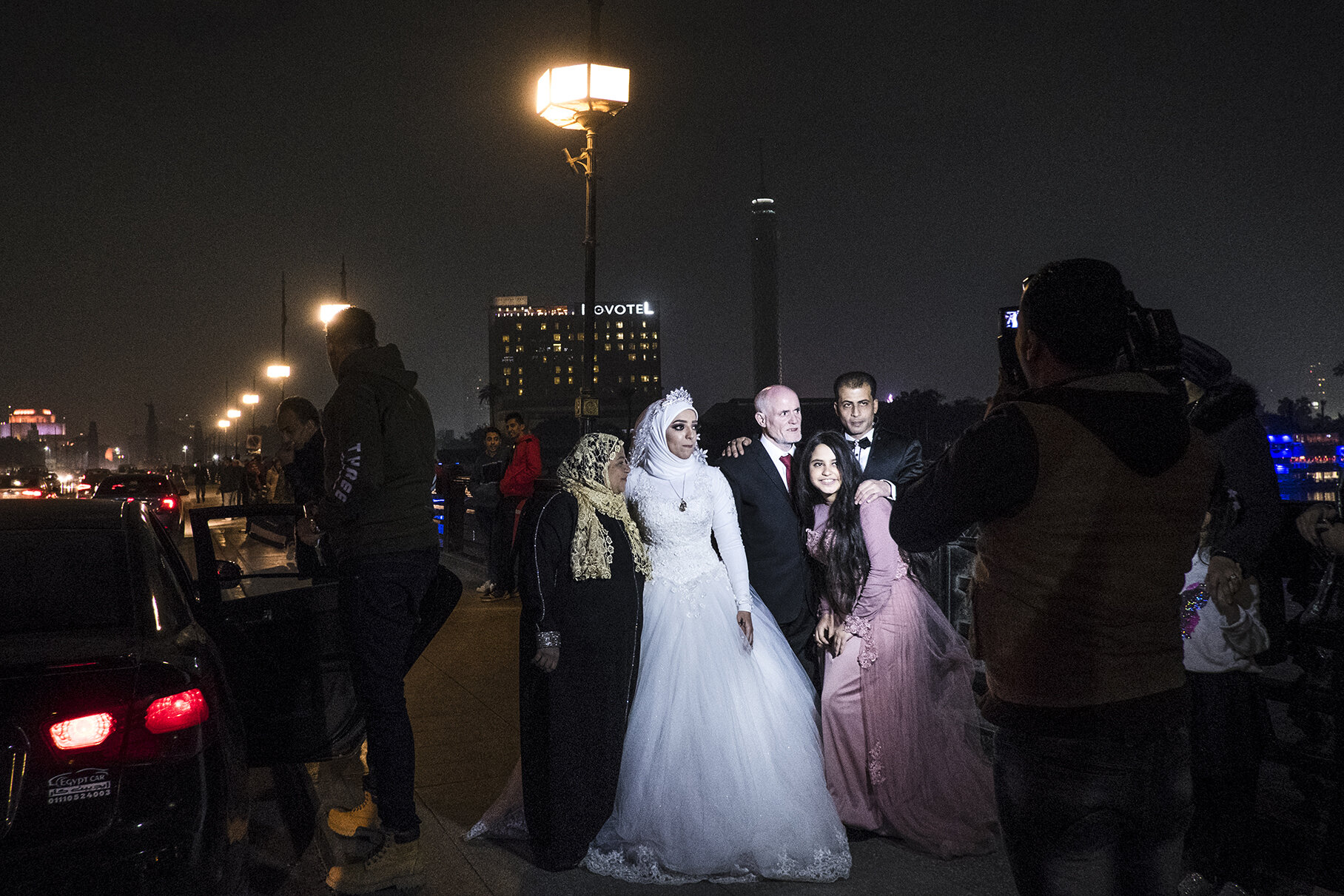 Together with her family, Gehad (25) poses for a traditional photo session on a bridge on Nile just after her wedding ceremony. In the life of Egyptian women, a wedding day is still considered a crucial moment of passage. Brides virginity, and in some social classes also circumcision, are necessary for finding a wealthy and appropriate husband. Large number of marriages are still arranged by the families and a future husband, often much older than his wife, is demanded to pay a price for a bride to her family and provide a place where they are going to live together after the ceremony.Women are expected to get pregnant as soon as even 2 months after the ceremony. Lack of pregnancy can lead to a divorce or give the husband permission to remarry. January 2019, Cairo, Egypt