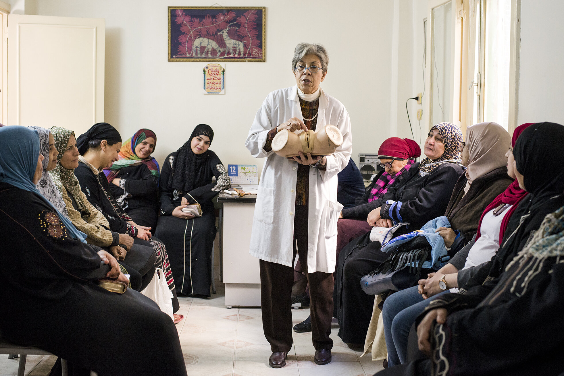 Dr. Mawaheb al Mowelhy is giving a seminar on the negative consequences of Female Genital Mutilation to the women gathered in a clinic located in an urban poor community in Cairo.The gynaecologist, after completing her PHD in Harvard, came back to Egypt where since 1994 she fights against the practice of female circumcision. Despite the criminalisation of the procedure and connected efforts of authorities, NGOs and even religious leaders, in some areas up to 80% of women are still being circumcised. After several cases of deaths of young girls after unsafe procedures, FGM has recently been mostly provided by medical practitioners who financially benefit from the situation. December 2018, Cairo, Egypt