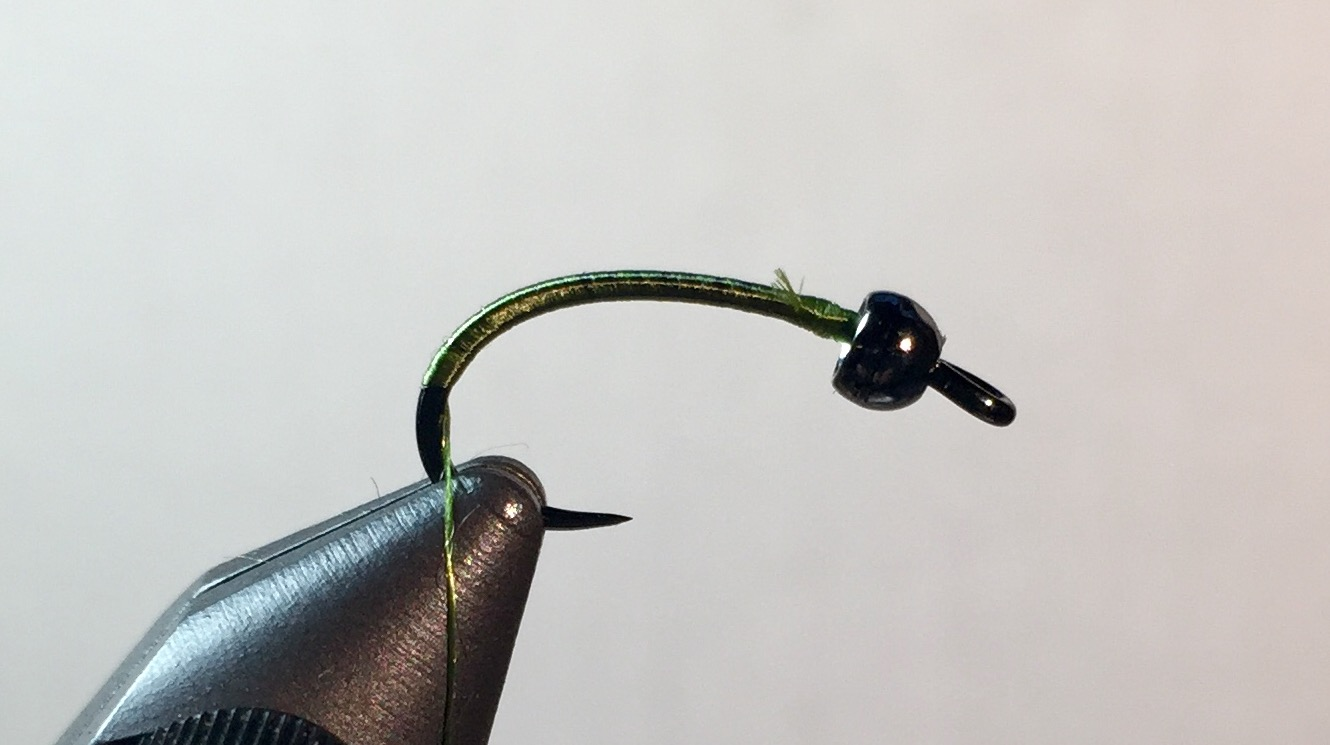 Step 1:  Slide bead on hook and place in vise. Start thread behind bead and wrap half down the bend.