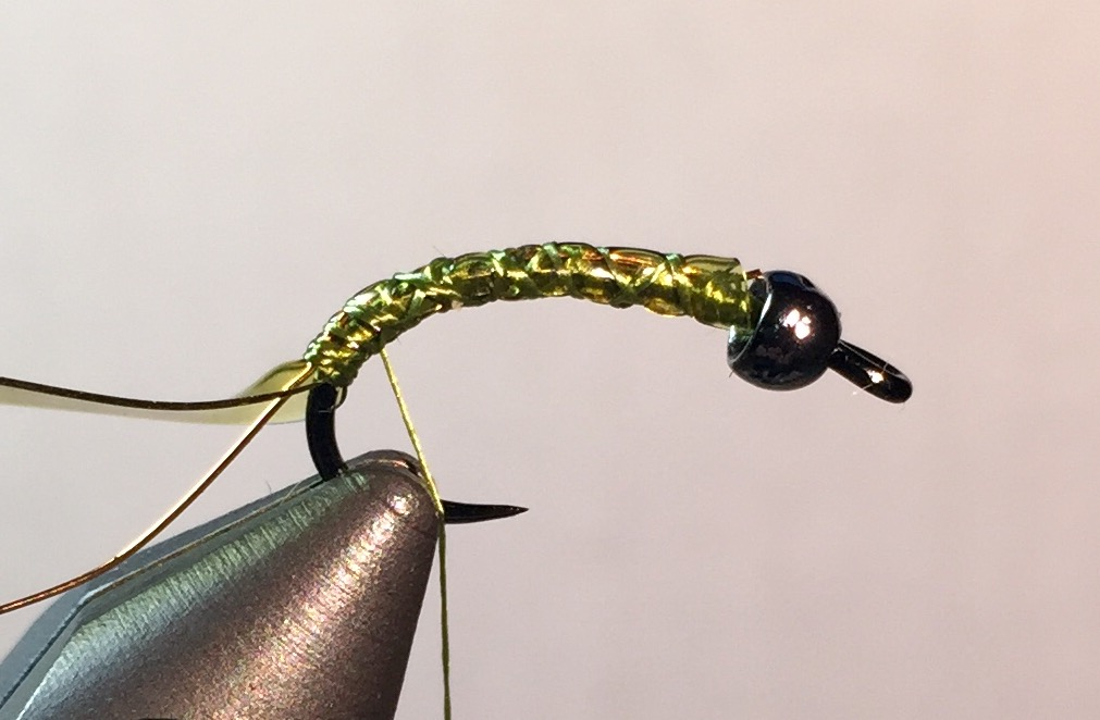 """Step 2:  Tie in a 2"""" section of fine copper wire, followed by a 1-1/2"""" section of olive Body Glass. Tie both the entire length of the shaft, up to the bead to build up the body."""