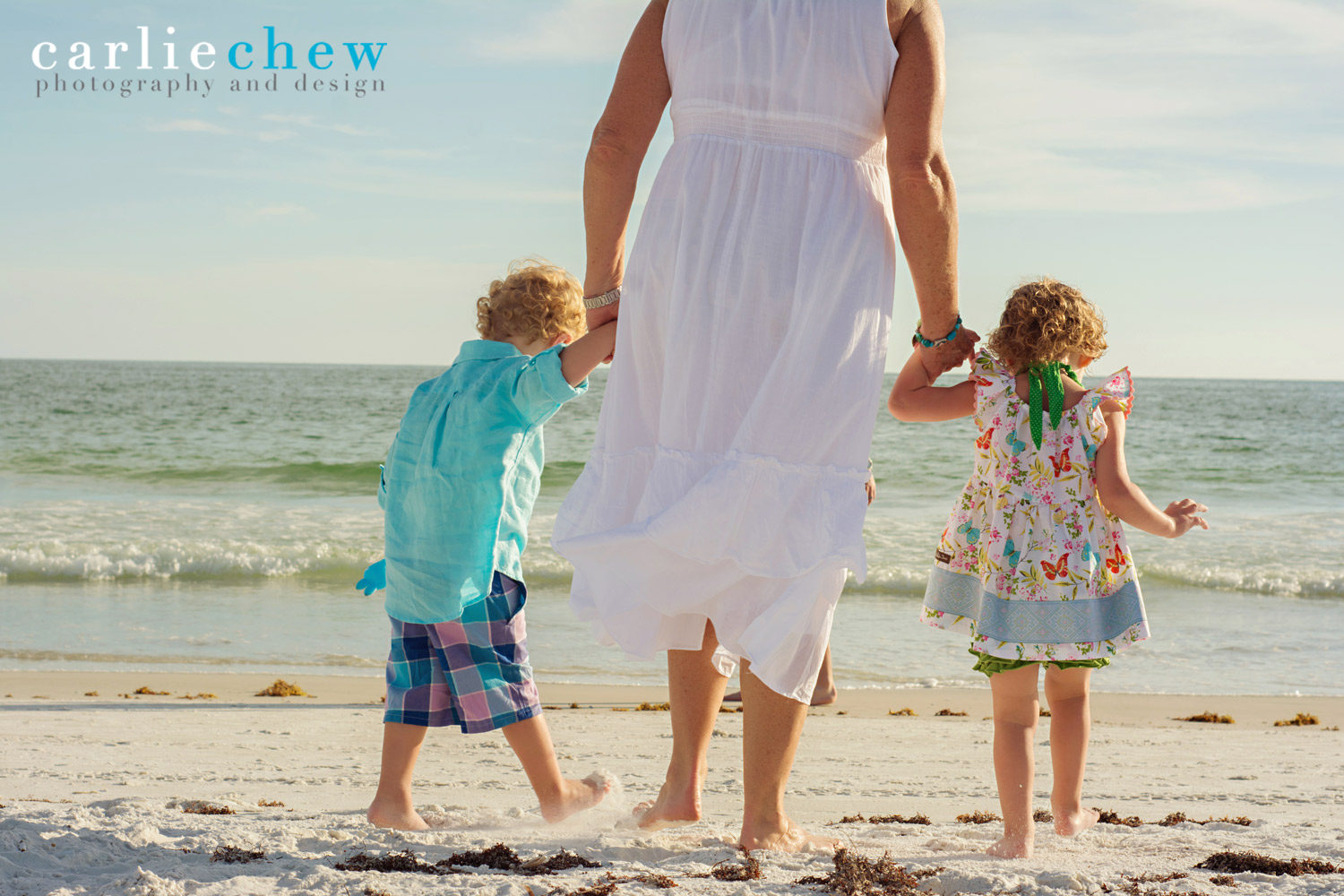 Grandmother walks down beach at Anna Maria Island while holding her grand children's hands with Carlie Chew Photography