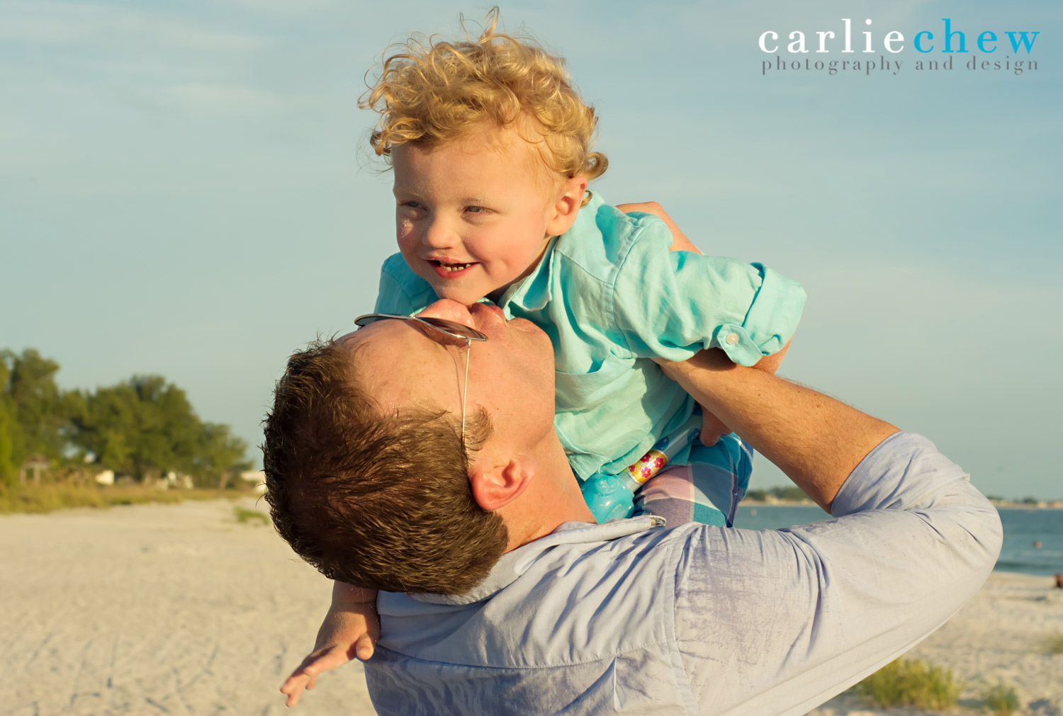 Father kisses happy son while playing at Anna Maria Island in Florida with Carlie Chew Photography