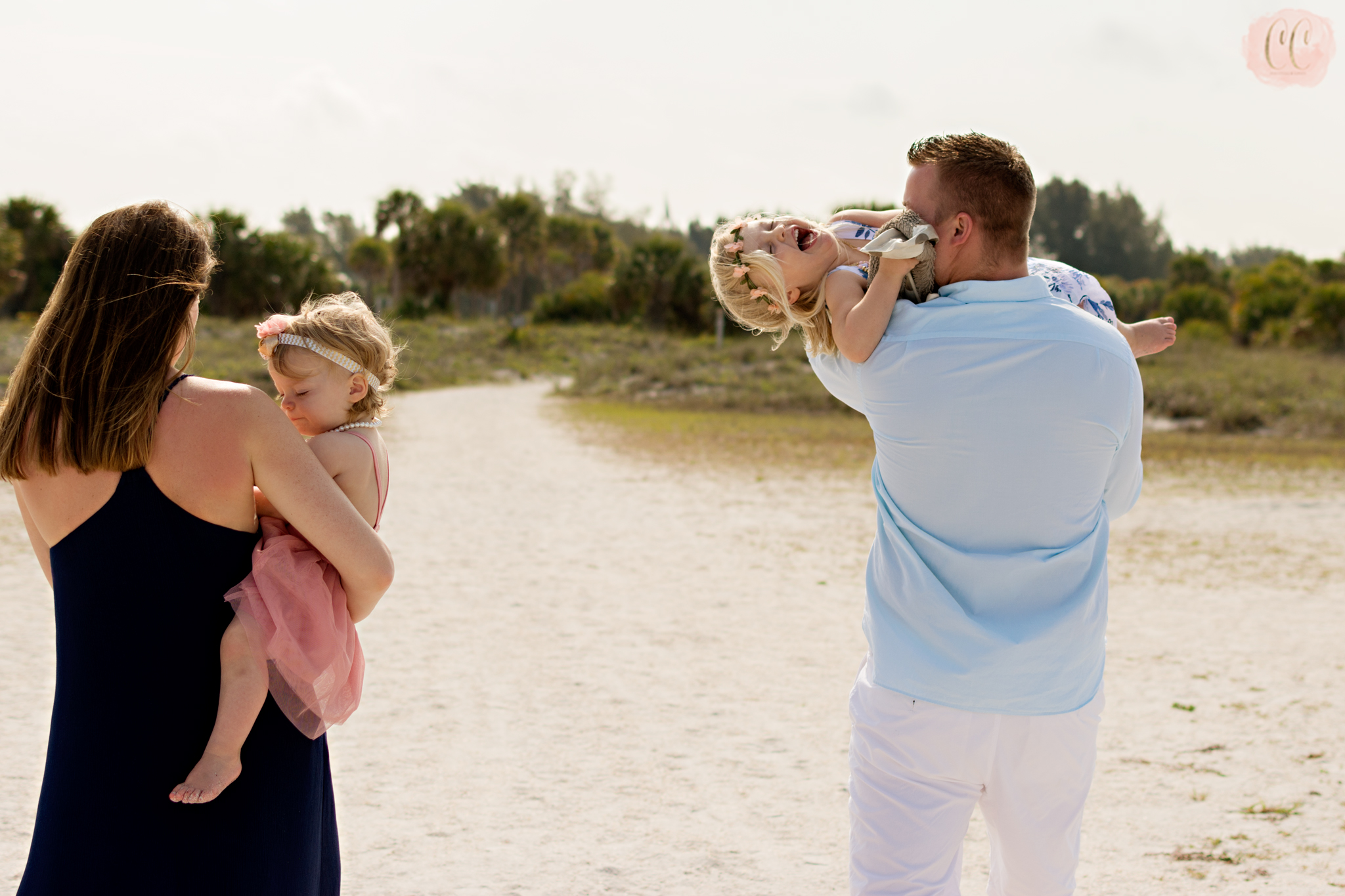 Child laughs in Dad's arms at Sand Key Park, Clearwater by Florida family vacation photographer Carlie Chew Photography