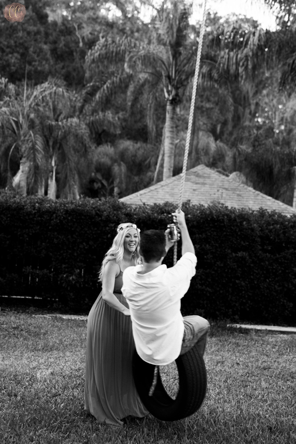 Pregnant woman pushes husband on tire swing with beer in hand in Odessa, Florida for maternity photographer Carlie Chew Photography
