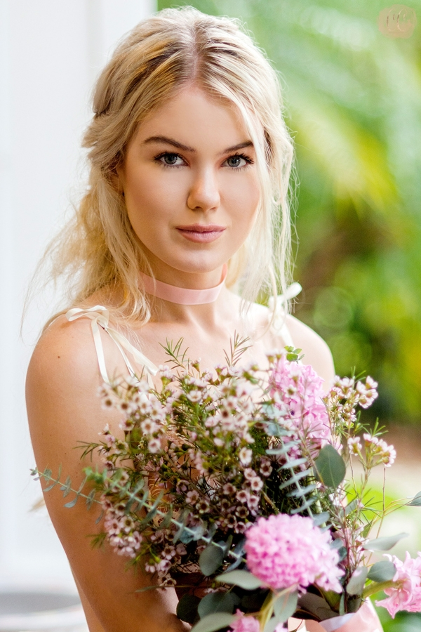 Beautiful pastel portrait of model with floral bouquet poses for Tampa fashion photographer Carlie Chew Photography