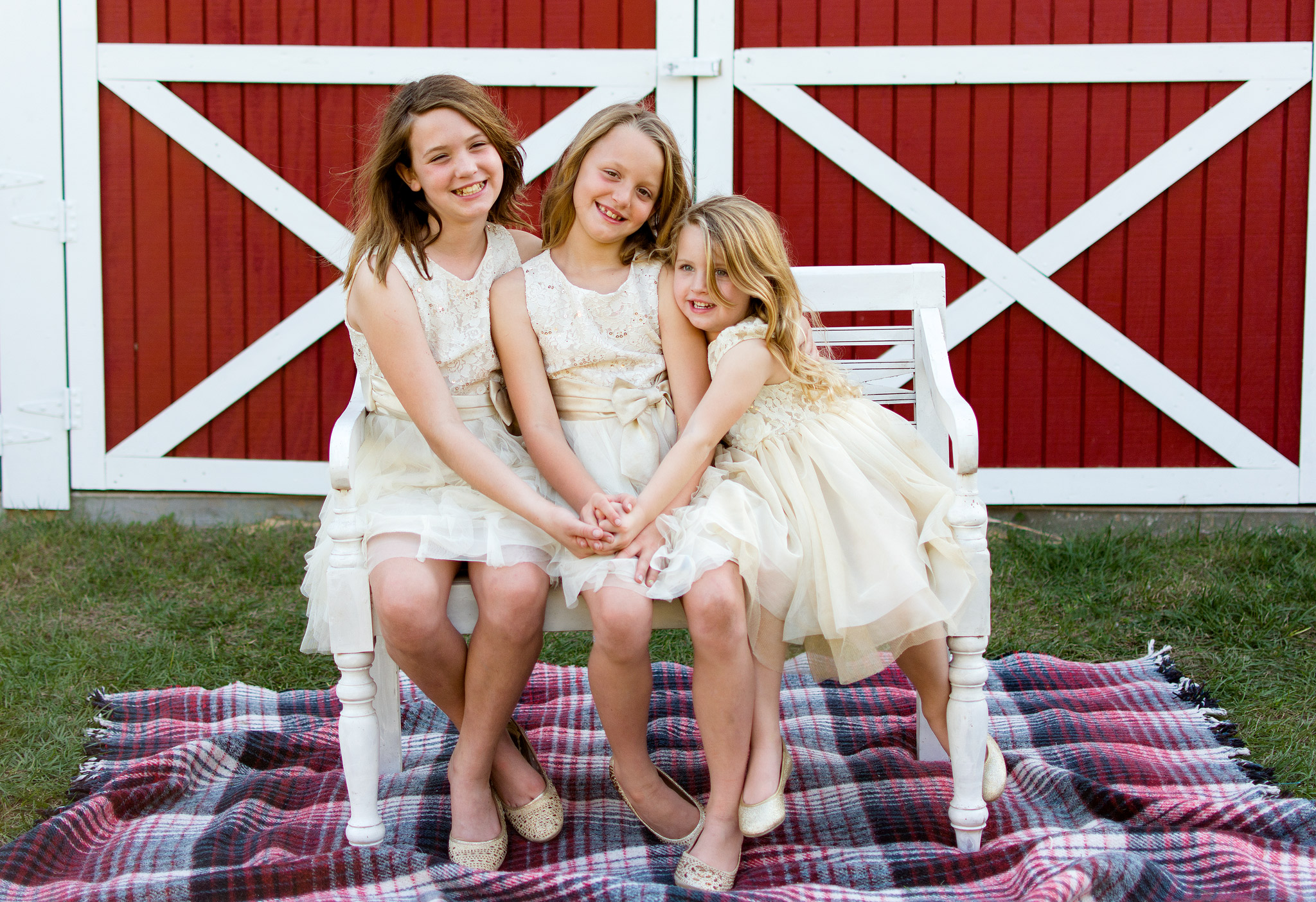 Adorable sister's hugging each other on a bench in front of barn in Dade city, Florida taken by Carlie Chew Photography